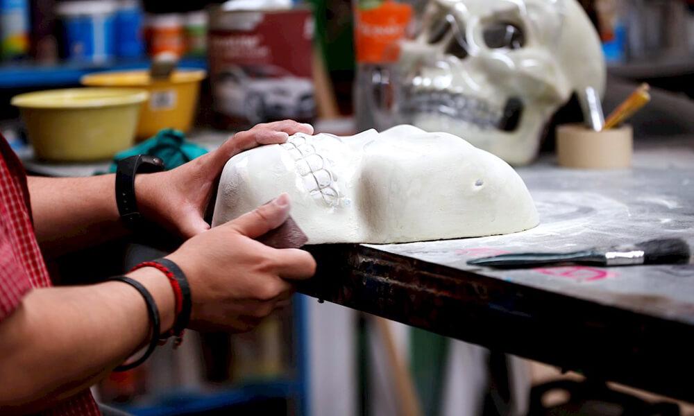 Elaboración de caretas de calavera en taller El Volador